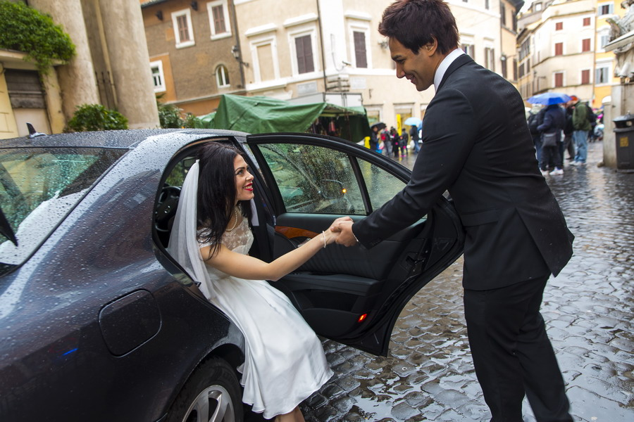Picture of the bride entering the car in the roman street.