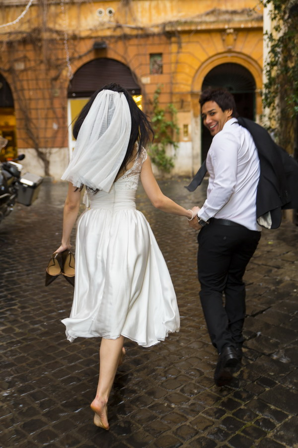 Bride and groom running during a wedding photo shoot on Via Margutta in Rome color version