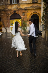 Newlyweds running by Via Margutta in Rome Italy during a wedding photo shoot
