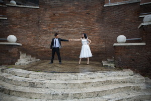 Bride and groom touching hands on Via dei Fori Imperiali in Rome
