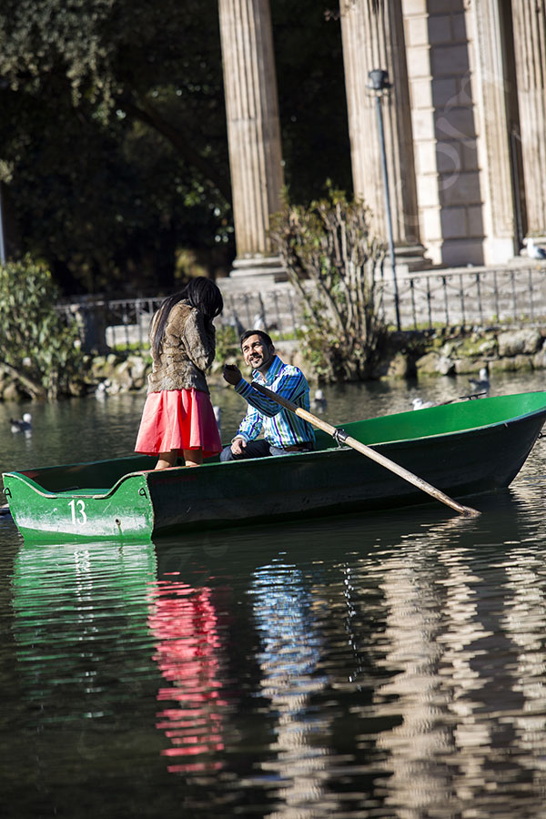 Man romantically showing engagement ring during a wedding proposal on a lake boat Villa Borghese