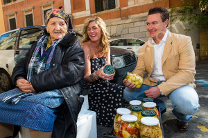 Couple having fun talking with an old lady selling hearty chokes in Rome Italy