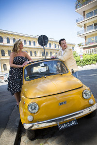 Couple posing by an old fiat 500 cinquecento in Rome Italy