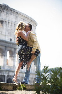 Romantic couple kissing in front of the Roman Coliseum in Rome Italy