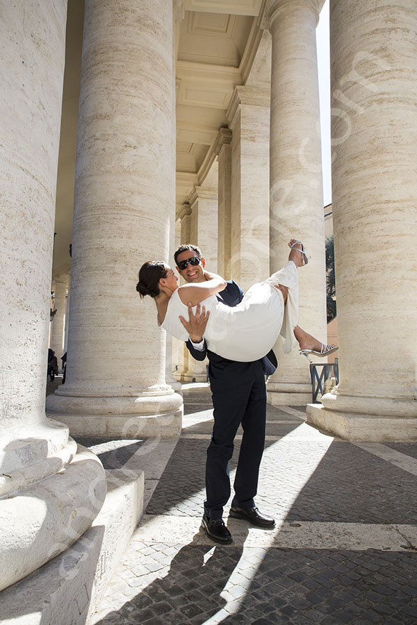 Newlywed couple in Saint Peter's square. Underneath the columns.