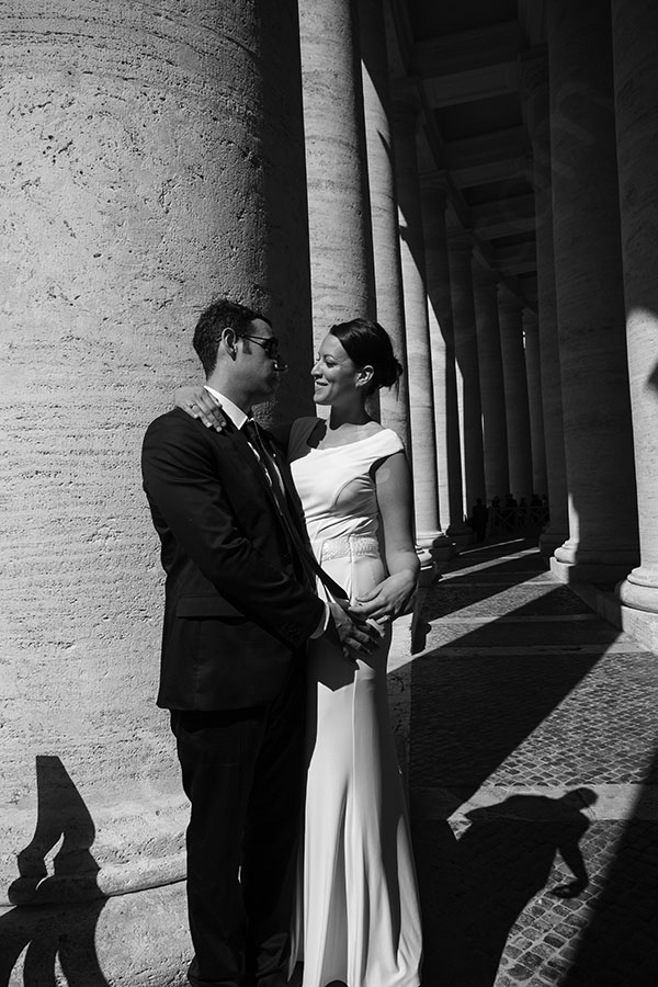 Couple posing for a picture at the Vatican under the stunning columns.