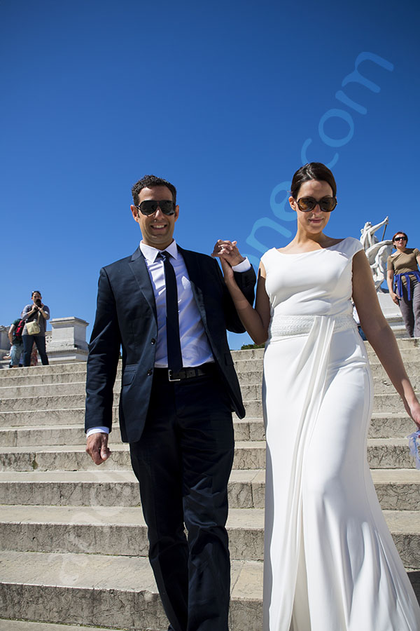 Bride and groom walking hand in hand down the stairs of the Vittoriano monument