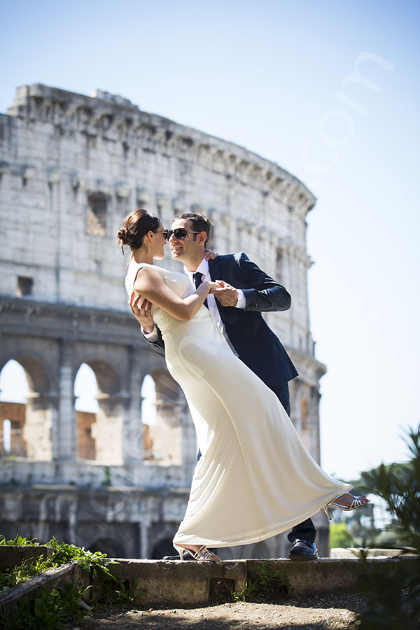 Newlyweds at the Roman Colosseum on a romantic pose.