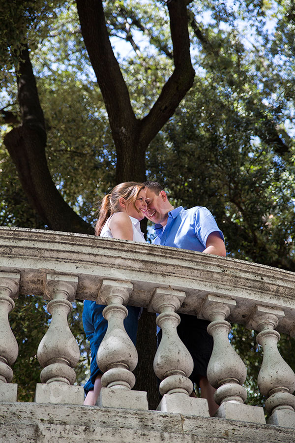 Couple kissing during a picture session over a balcony.