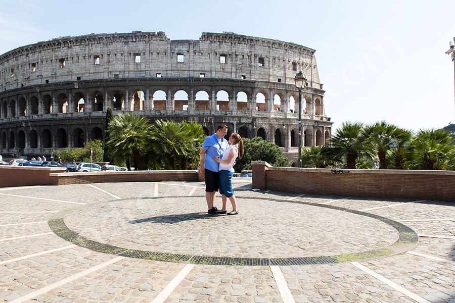 Couple posing at the center of a circle in a piazza by the Roman Colosseum