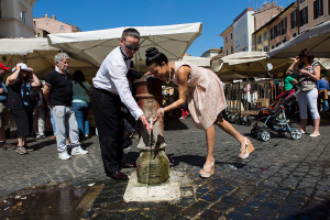 Engagement couple drinking water from a water fountain in Piazza Campo dei Fiori in Rome Italy