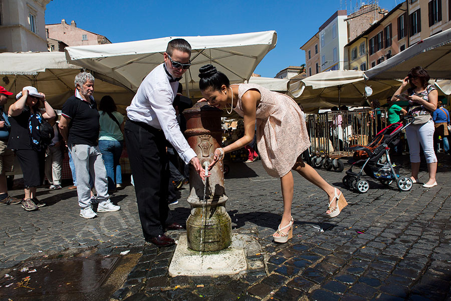 Newlyweds drinking water from a fountain in Piazza Campo dei Fiori