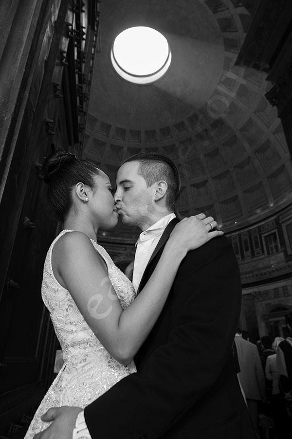 Kissing at the Roman Pantheon by the entrance of the structure. Light shining through the hole.