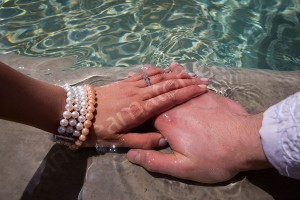Couple hands with the engagement ring immersed in water at the Gianicolo water fountain in Rome
