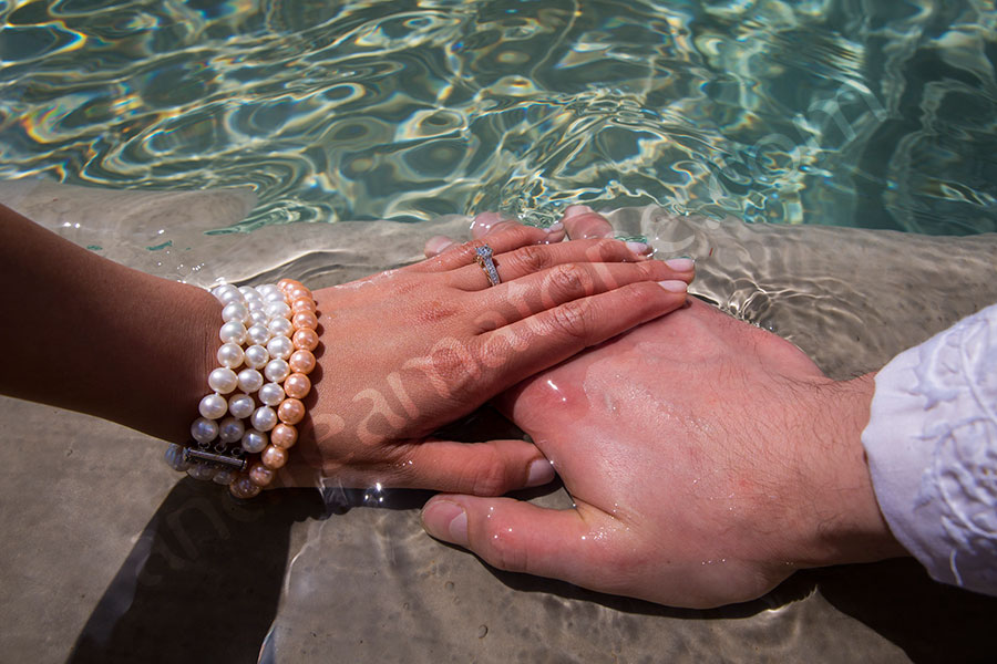Hands with the engagement ring immersed in water at the Gianicolo fountain