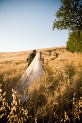 Bride and Groom in Tuscany Italy. Walking away in a field. Countryside.