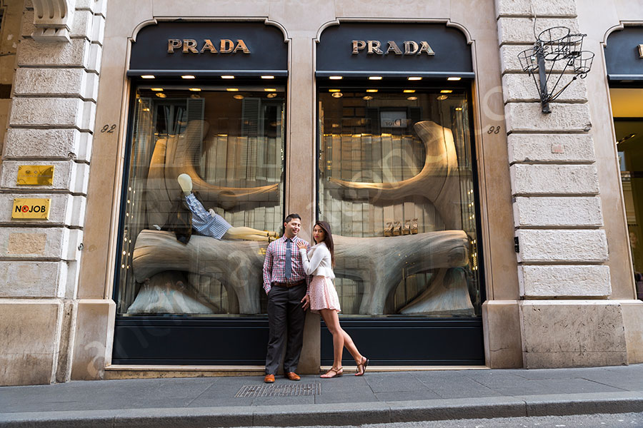 Engagement photographer picture posing in front of the Prada showcase