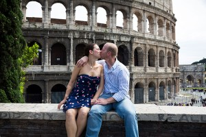 Honeymoon couple kissing in front of the Roman Colosseum in Rome Italy