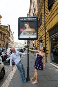 Couple photographed in around a Tiziano museum poster on the streets