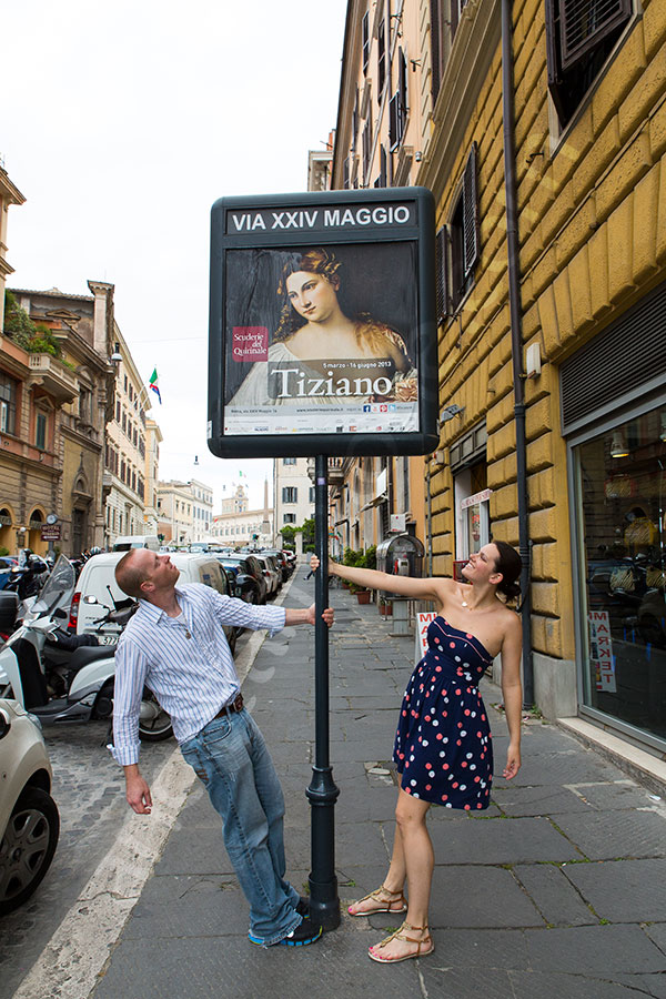 Couple in around a Tiziano museum poster on the streets