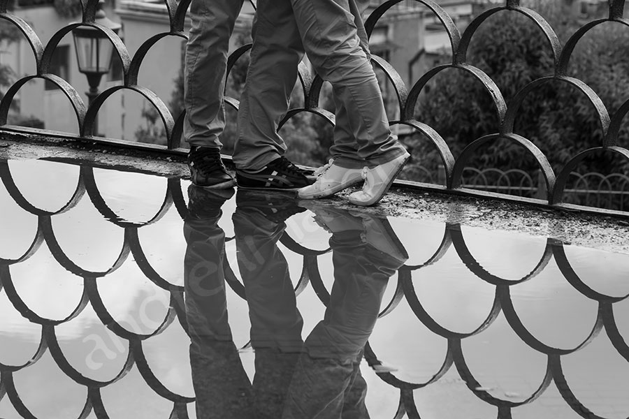 Close up feet over puddle reflection