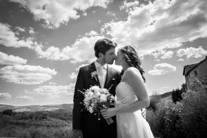 Bride and groom kissing under Tuscany sky in Italy