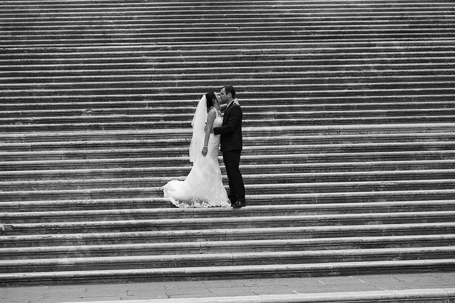 Newlyweds couple kissing on the stairs of Piazza del Campidoglio