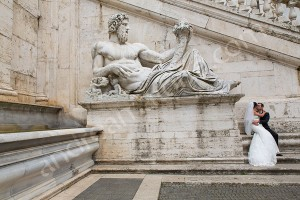 Wedding couple photographed next to a statue in Piazza del Campidoglio in Rome Italy