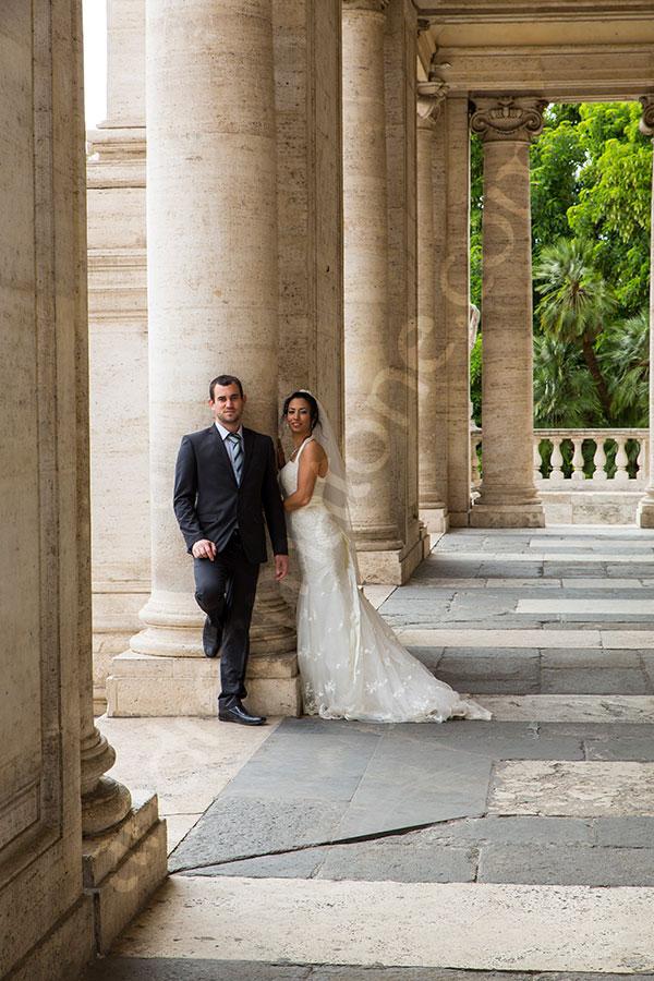 Newlyweds posing underneath columns found in Piazza del Campidoglio