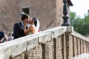 Wedding couple kissing on Tiber island bridge in Rome