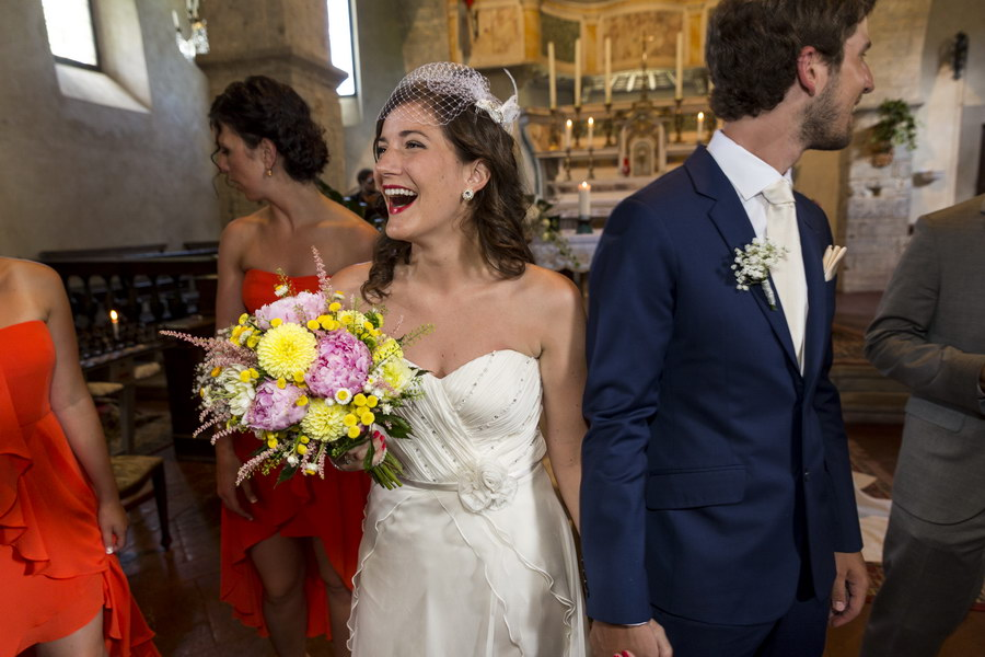 Happy newlyweds exit Church Castello di Spaltenna in Gaiole in Chianti