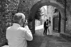 Wedding photographer taking a picture of the bride and groom in black and white