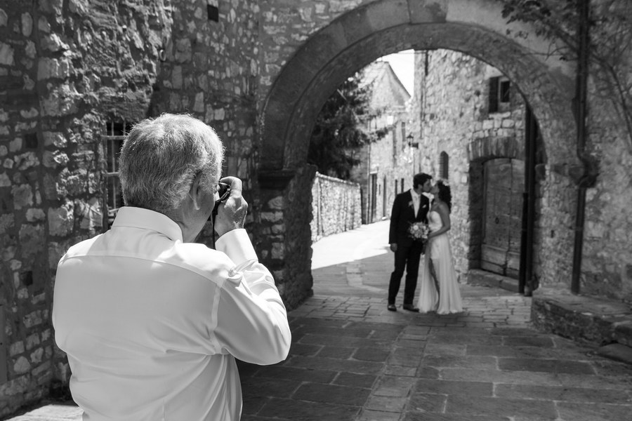 Photographer taking a picture of the newlyweds in black and white