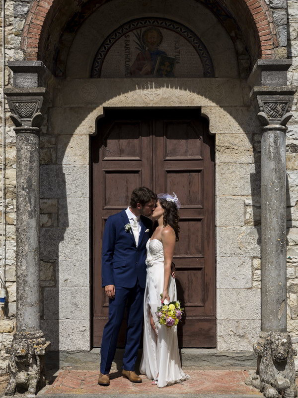 Kissing at the doorsteps of an old Church in Tuscany