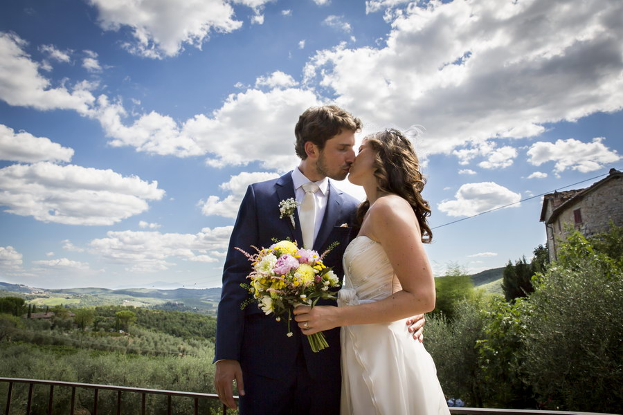 Tuscany Wedding Photographer Kissing before the Tuscan hills in Gaiole in Chianti