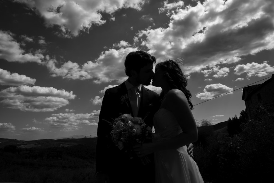 Black and white version of couple under fluffy clouds