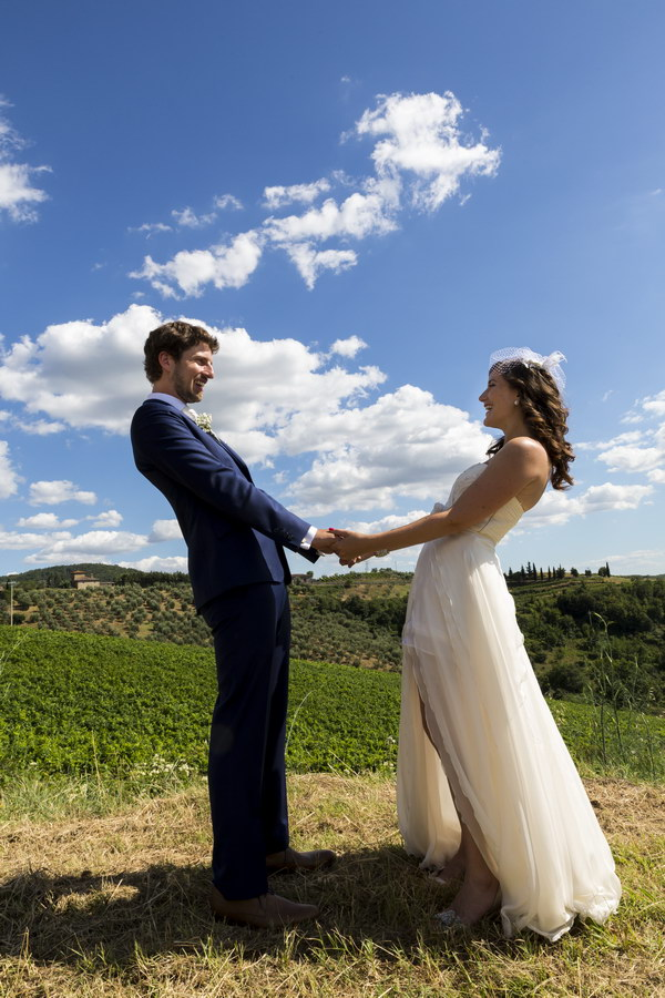 Just married couple holding hands over the beautiful Italian countryside.