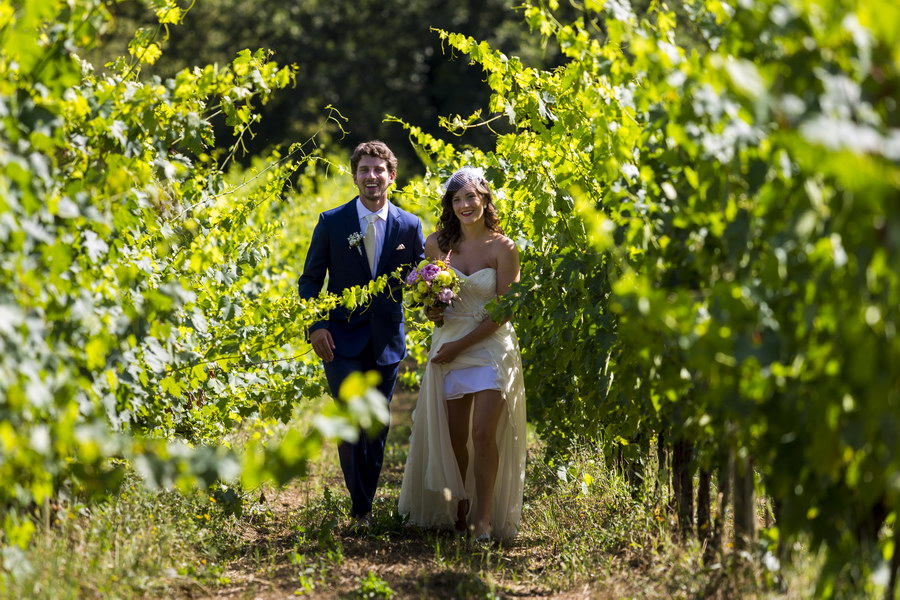 Bride and groom walking in a vineyard in Tuscany Italy Wedding Photographer