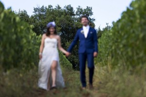 Wedding picture out of focus as newlyweds walk in a Tuscan vineyard in Italy