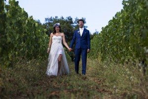 Wedding picture in focus photo as newlyweds walk in a Tuscan vineyard in Italy