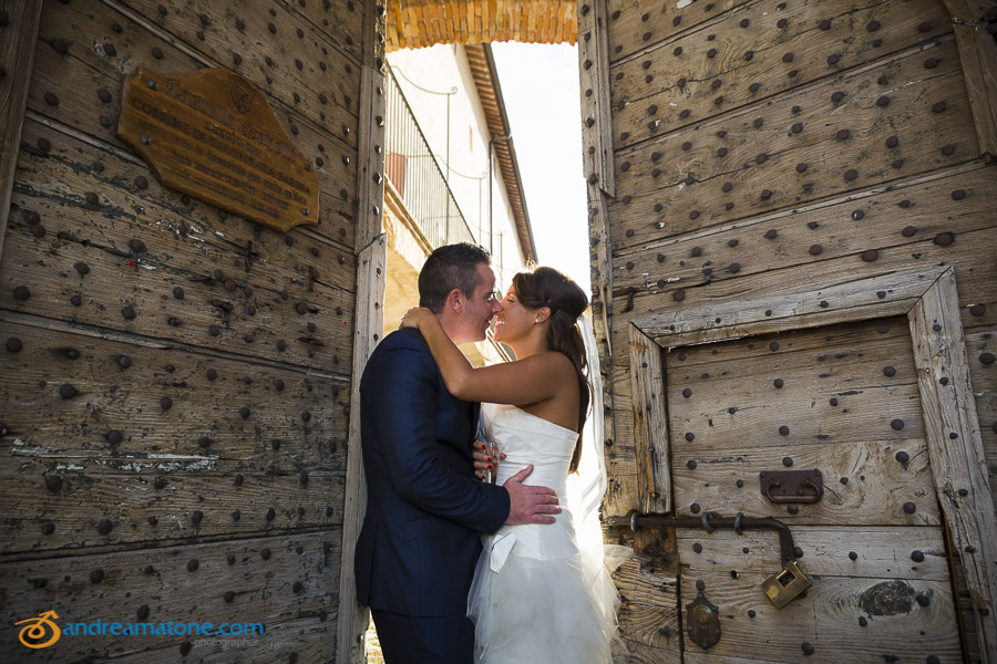 Bride and groom kissing at the doors of Castle Savelli Palombara Sabina Italy