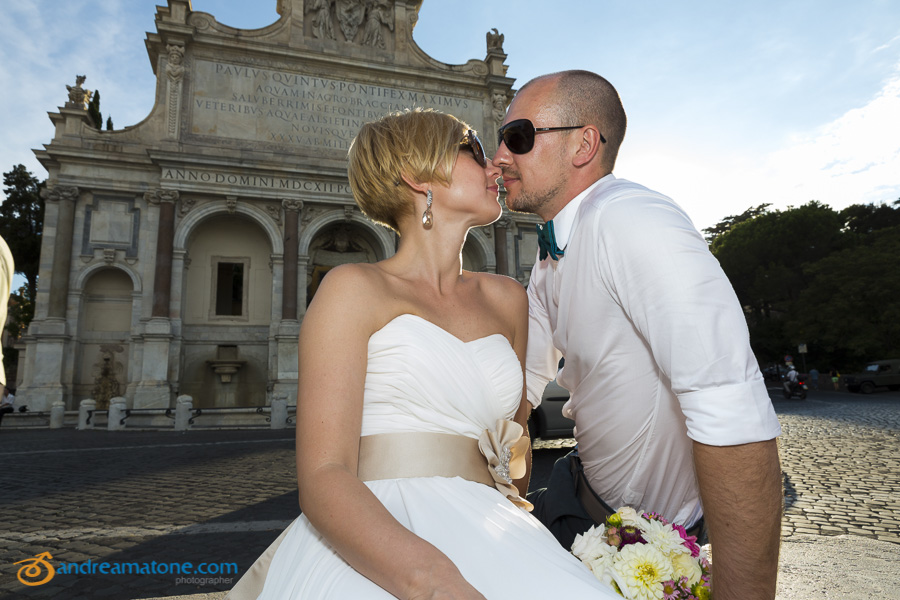 Kissing in front of the Gianicolo water fountain: Rome wedding photographer