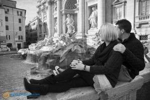 Couple photographed from behind while looking at the Trevi fountain in Rome Italy.