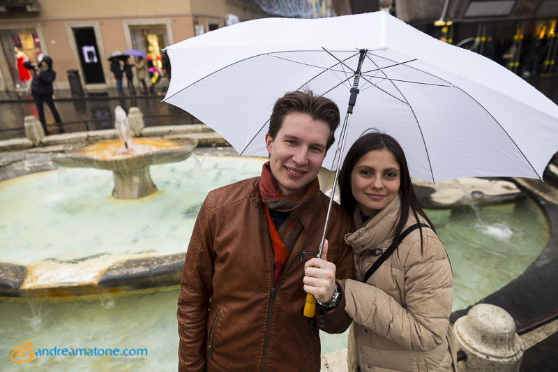 An engagement couple at the Spanish steps fountain with an umbrella.