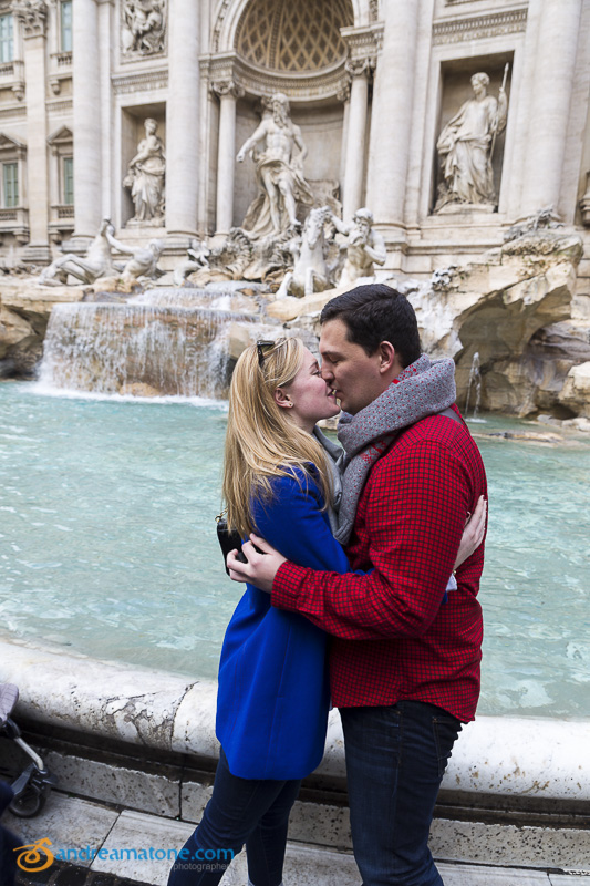 Couple just engaged during a marriage proposal at the Trevi fountain.