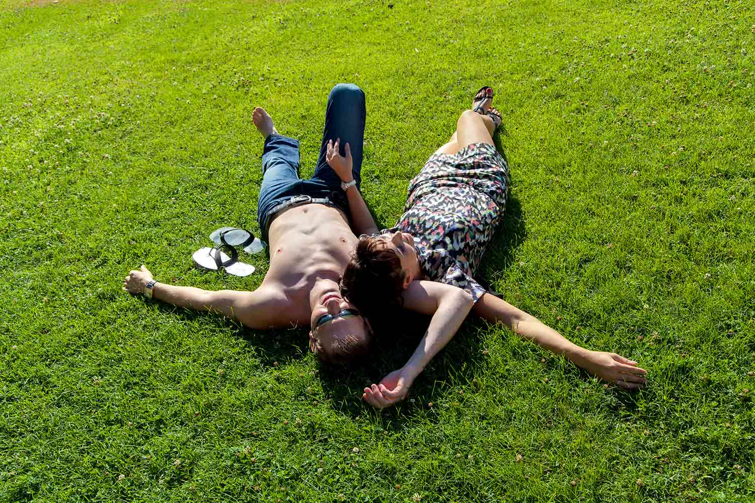 Laid back couple relaxing on green grass.