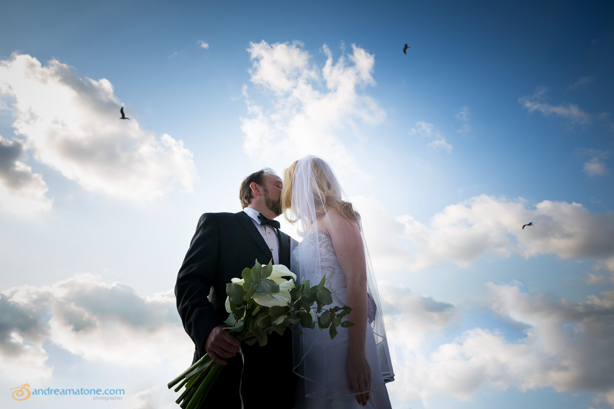 Newlyweds kissing underneath blue sky.