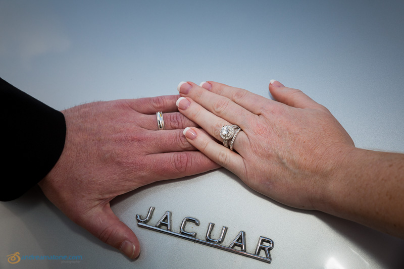 Hands together with rings on the Jaguar vintage car