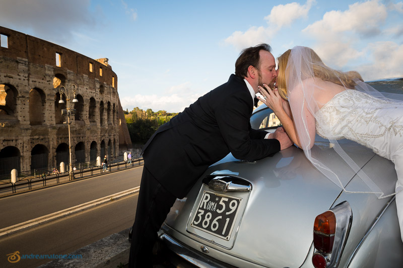 Kissing on a classic vintage car in Rome in front of the Colosseum. Destination wedding photographer Italy.