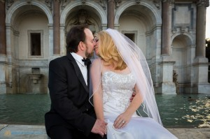 Couple kissing in front of the Gianicolo water fountain in Rome Italy.